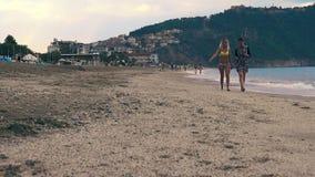 De meisjes lopen op het strand stock videobeelden