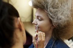 De meisjes met een weelderige kapselgrimeur maakt samenstelling royalty-vrije stock afbeelding