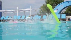De meisjes met opblaasbare ringen en de matras springen in pool, joyfull weekend van meisjes in zwempakken in poolside, stock video