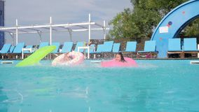 De meisjes met opblaasbare ringen en de matras springen in poolside, joyfull weekend van meisjes in badpakken in pool, stock video