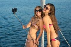 De meisjes met selfie plakken het glimlachen Royalty-vrije Stock Foto's