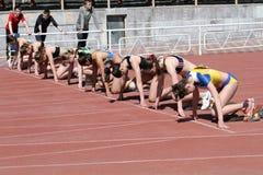 De meisjes op het begin van de 100 meters rennen Royalty-vrije Stock Afbeeldingen
