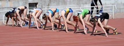 De meisjes op het begin van de 100 meters rennen Stock Afbeelding