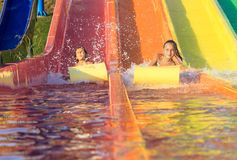 De meisjes op het water glijden Stock Foto's