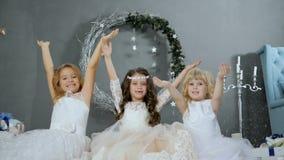 De meisjes op vooravond van Kerstmis met opgeheven handen vangen kunstmatige sneeuw bij studio op achtergrond van Nieuwjaar` s de stock videobeelden