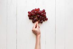 De meisjes` s hand houdt op een bos van rode druiven op een houten achtergrond Mening van hierboven De druiven zijn als ballons Stock Fotografie