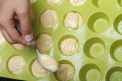 De meisjes` s hand zet deeg in siliciumvorm voor cupcakes Voorbereiding van eigengemaakt dessert voor thee Stock Foto