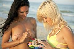 De meisjes schilderen elkaars door waterverven Stock Foto's