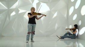 De meisjes spelen de viool lyrische samenstelling die zich in een witte ruimte bevinden stock footage