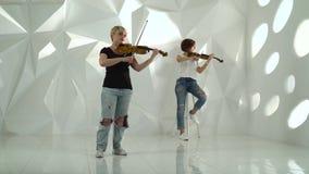 De meisjes spelen de viool lyrische samenstelling die zich in een witte ruimte bevinden stock video