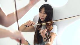 De meisjes spelen de viool lyrische samenstelling Sluit omhoog stock footage