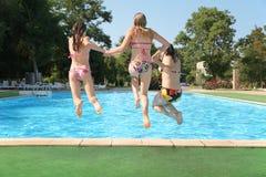 De meisjes springen in pool stock afbeeldingen