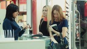 De meisjes tonen parfum op de tablet en kopen hen in winkel in wandelgalerij stock videobeelden