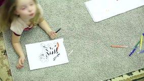 De meisjes trekken tellers in het album liggend op de vloer in de ruimte stock video