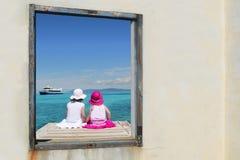 De meisjes van de zuster bekijken venster tropisch overzees turkoois Royalty-vrije Stock Afbeelding