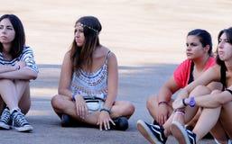 De meisjes van het publiek, sitted op de vloer, letten op een overleg in FIB (Festival Internacional DE Benicassim) Stock Afbeeldingen