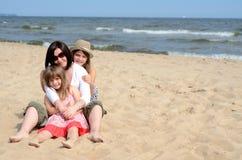 De meisjes van Huddled op het zonnige strand Stock Afbeeldingen