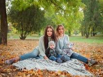 De meisjes van tweelingen en een kleine jongen en babyzitting in de herfst parkeren op een plaid royalty-vrije stock fotografie