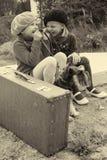 De meisjes vertellen elkaar geheimen, zittend bij de bushalte Stock Foto