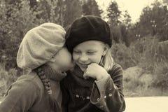 De meisjes vertellen elkaar geheimen, zittend bij de bushalte Stock Fotografie