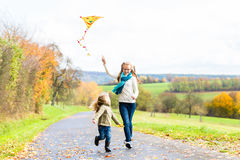 De meisjes vliegen een vlieger op de herfst of dalingsweide Royalty-vrije Stock Fotografie