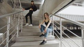 De meisjes vormen photoshoot op concrete treden, die in camera, industrieel stedelijk milieu stellen stock videobeelden