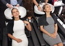 De meisjes wassen hoofd in de schoonheidssalon royalty-vrije stock afbeelding