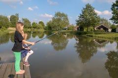 2 de meisjes zijn bij een schipbrug bij een meer vissen royalty-vrije stock afbeelding