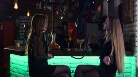 De meisjes zijn in een bar in de avond, roken een waterpijp, drinken cocktails en spreken met elkaar in langzame motie in 4k stock footage