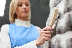 De meisjesarbeider voert droge Wasserij, kledingstukken van het hand de schoonmakende bont uit Royalty-vrije Stock Foto's