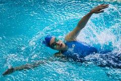 De meisjesatleet zwemt rugslag, rond haar nevel van water Royalty-vrije Stock Afbeelding