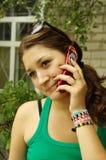 De meisjesbesprekingen op telefoon Stock Foto