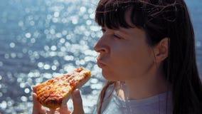 De meisjesbeten van stuk van pizza en kauwt het op achtergrond van overzees stock video