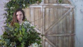 De meisjesbloemist houdt een vaas van bloemen in haar handen, die haar gezicht verbergen stock foto's