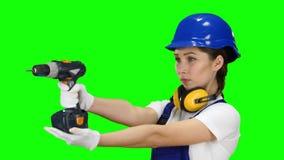 De meisjesbouwer houdt een boor in zijn handen en kijkt rond Het groene scherm Sluit omhoog stock video