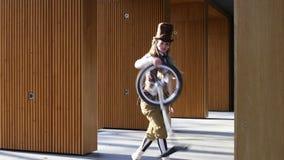 De meisjesclown berijdt een unicycle en jongleert met een fiets stock videobeelden