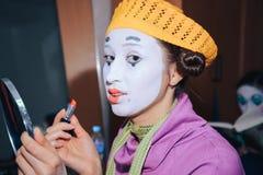De meisjesclown in de gele hoed krijgt de definitieve aanrakingen van make-up, samenvattend de lippenstift royalty-vrije stock afbeelding