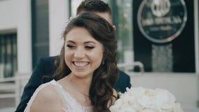 De meisjesdraaien scherp aan de camera en de glimlachen, en achter haar komt haar vriend stock footage