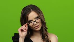 De meisjesflirts, bijt haar lip, is zij sexy en zachte kledingsglazen Het groene scherm Sluit omhoog stock videobeelden