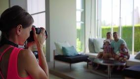 De meisjesfotograaf neemt een familiebeeld aan de camera in de zaal op een opgeschort bed, langzame motie stock footage