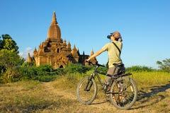 De meisjesfotograaf op een fiets neemt een beeld binnen van de tempel stock afbeeldingen