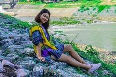 De meisjesglimlach en zit op de rotsvoorzijde van Dambrug stock foto
