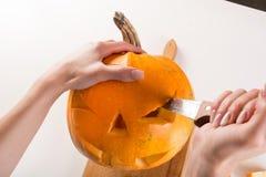 De meisjeshand maakt hefboomo lantaarns voor Halloween-vakantie met keukenmes royalty-vrije stock afbeelding