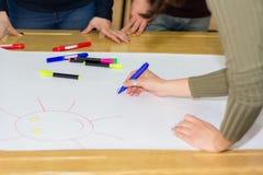 De meisjeshand met blauw voelde pen trekkend op groot Witboek op bureau in klaslokaal stock foto's