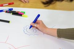 De meisjeshand met rood voelde pen trekkend op oranje document op bureau in klaslokaal royalty-vrije stock foto