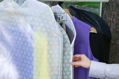 De meisjeshand neemt kleren die op een hanger in een dekking hangen Close-up stock afbeeldingen