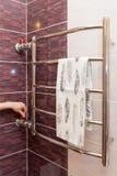 De meisjeshand regelt de waterkraan in het verwarmde handdoekspoor Stock Afbeelding