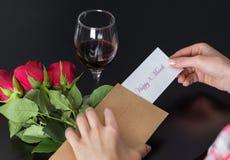 De meisjeshanden neemt een bericht Gelukkige 8 Maart op document van de retro envelop op zwart bureau met rood roze boeket en rod royalty-vrije stock fotografie