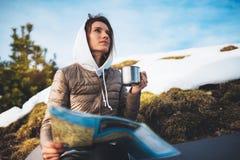 De meisjesholding in handenkop dranken, toerist kijkt op kaart, mensen die reis in sneeuwberg plannen, hipster op de achtergrondw stock foto's