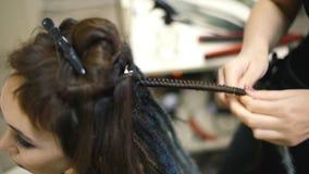 De meisjeskapper weeft dreadlocks cliënt in de salon stock videobeelden